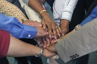 A group of co-workers touching hands in a circle.
