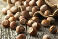 Hazelnuts spilling from a sack onto a wood table.