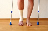 Man with bandaged foot on crutches