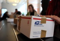 Customers wait in line to deliver packages at post office