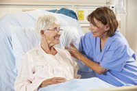 A hospice nurse talks to an elderly female patient