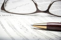Close up of financial documents with glasses and a pen.
