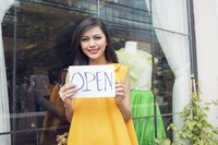 A fashion designer holding an open sign in front of her boutique.