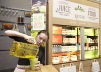 An employee making a smoothie in a fresh juice store.