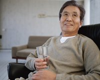Mature man holding a glass of water.