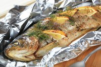 Baked trout stuffed with lemon and wrapped in foil