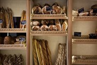 A wall of freshly baked breads in a bakery.