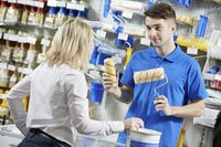 A hardware store employee compares products for a customer