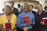 Members of a church hold their bibles while standing.