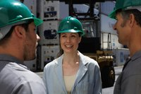Men and women on a jobsite are wearing safety helmets.