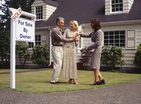 Real estate agent handing mature couple a set of keys.