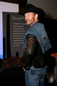 Musician Keith Burns poses in front of a Wrangler jeans display at an industry event.
