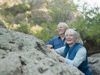 Smiling retired couple out on a hike.