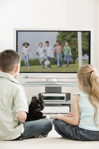 Cats and kids have been known to watch television together.