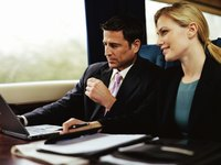 A businessman and woman are at work on their commute.