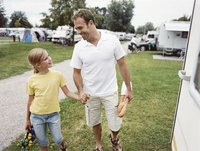 Father and daughter walking through an RV campgrounds.