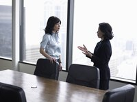 Two businesswomen talking in a conference room.