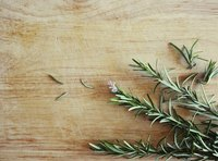 A sprig of freshly cut rosemary on a cutting board.