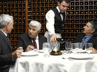 Waiter serving wine to restaurant customers at table