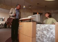 A man speaking with a woman at a medical office reception desk.