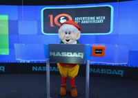The Keebler Elf is standing behind a NASDAQ sign.
