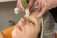 A client receiving an eyebrow wax in a salon.