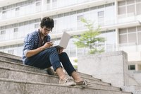 A writer sitting on a campus stairwell outside with a laptop and smartphone.