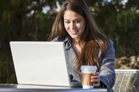 Woman with coffee and laptop and outdoor cafe.