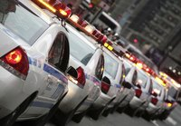 A long line of police squad cars drives down a city street