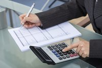 Close-up of woman working on taxes at table with calculator.