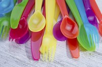 Multi-colored plastic cutlery on a table surface
