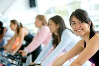 Woman exercising in spin class at fitness club.