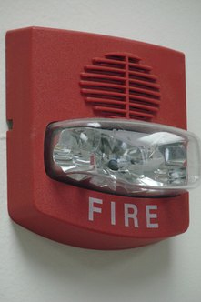 Alarms with flashing lights provide visual aid for those with hearing impairments.