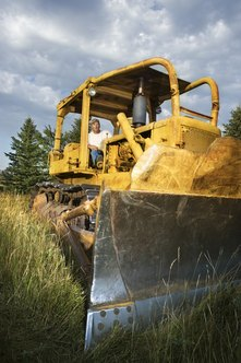 A bulldozer operator usually completes an apprenticeship before qualifying for a permanent job.