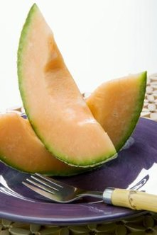 The fruits of cantaloupe plants have soft orange meat surrounded by a rough brown skin.