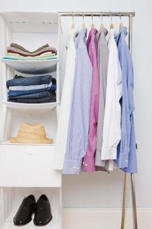 A canvas organizer, hung from a closet rod, provides storage for folded clothing.
