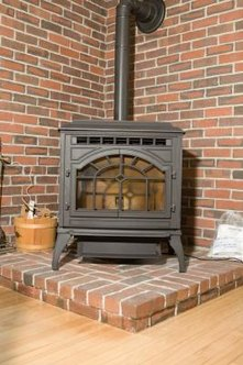 Enlist a contractor to install the stove pipe where a wall has brick veneer.