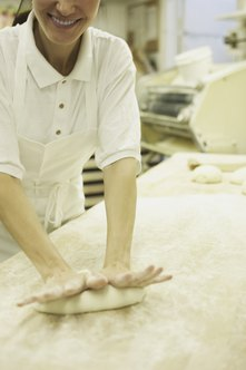A baker kneads a loaf of bread dough.