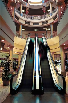 The common areas in a shopping mall include escalators, hallways and decorations.
