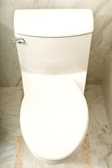 Tightening a toilet's flange bolts on an uneven surface may crack the base.