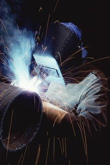 Pipe welders use protective gear to weld pipes together.