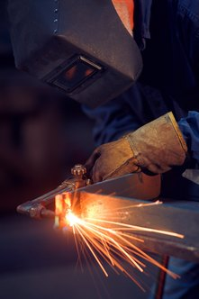 Welders use tools to join metal components.