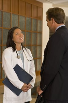 Healthcare administrators meet with physicians to ensure quality patient care.