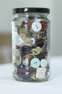 Manipulatives, such as a jar of buttons, can help engage students in descriptive writing.