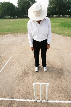 Cricket umpires check the stumps before a match begins.