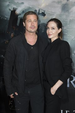 Angelina Jolie and Brad Pitt stop for photographers before entering a 2013 movie premiere.