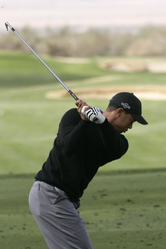 Tiger Woods' hands remain in front of his upper right chest near the top of his backswing.