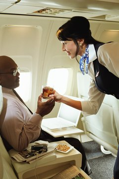 Flight attendants serve food and drinks to passengers.
