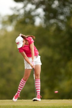 As she hits the ball, LPGA Tour player Paula Creamer's upper body is still between her feet and not yet over her left leg.