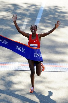 Firehiwot Dado crosses the finish line of the 2011 NYC Marathon.